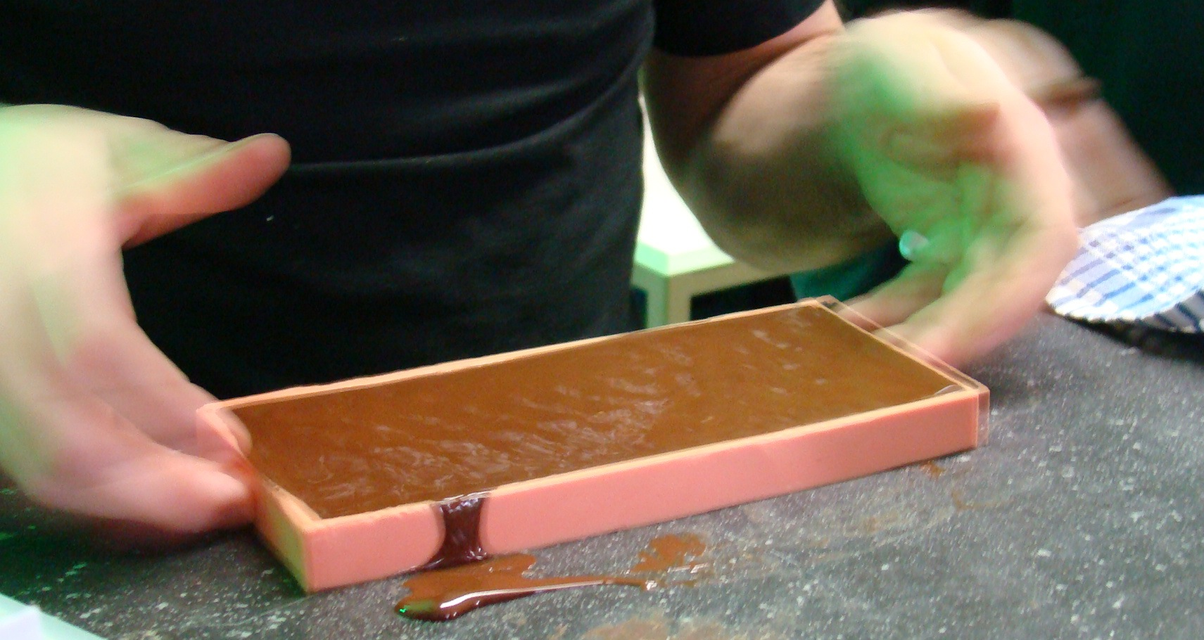 Shaking the poured chocolate in order to release air bubbles.