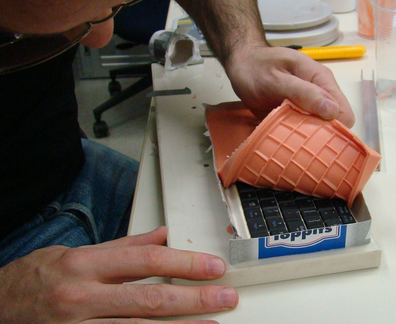Georges peels the new silicone mold off the keyboard